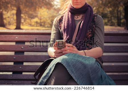 A young woman is sitting on a park bench in autumn and is using her phone - stock photo