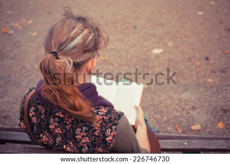 A young woman is sitting on a park bench in the autumn and is reading a book