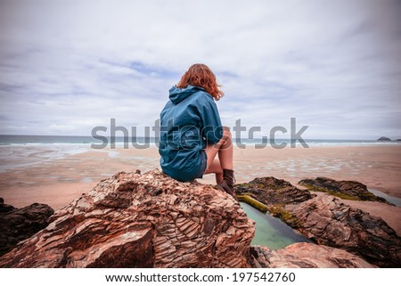 A young woman is sitting on a rock on the beach - stock photo