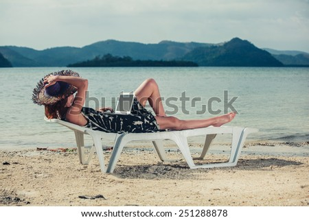 A young woman is sitting on a sunbed on a tropical beach and is working on a laptop