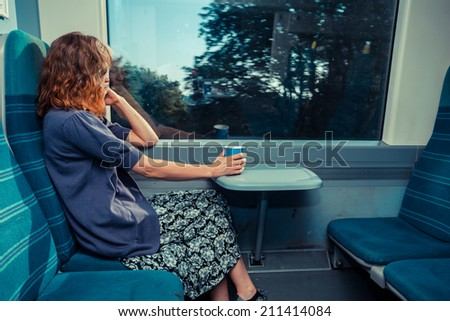 A young woman is sitting on a train with a cup of coffee and is looking out - stock photo