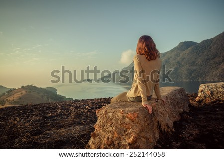 A young woman is sitting on an unusual rock on a mountain overlooking a bay at sunrise in a tropical climate - stock photo