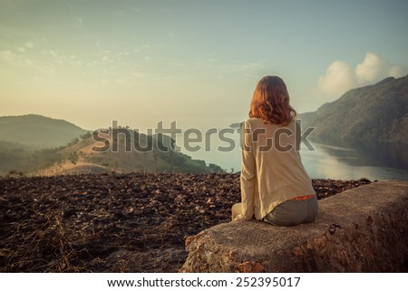 A young woman is sitting on an unusual rock on a mountain overlooking a bay at sunrise in a tropical climate