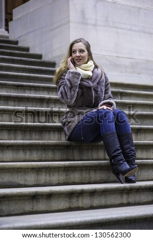 A young woman is sitting on stairs and talking on the phone./Girl Talking on Phone