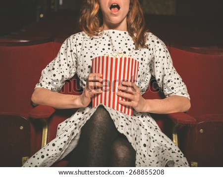 A young woman is sitting on the front row in a movie theater and is watching an exciting film while eating popcorn - stock photo