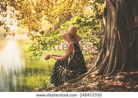 A young woman is sitting under a tree by the river - stock photo