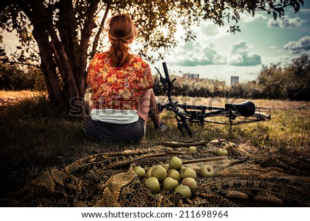 A young woman is sitting under a tree with a bunch of apples and a bicycle - stock photo
