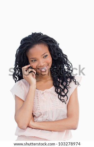 A young woman is smiling and talking on the mobile phone - stock photo