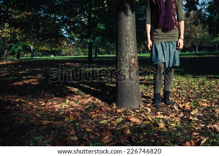 A young woman is standing by a tree surrounded by fallen leaves in a park on an autumn day