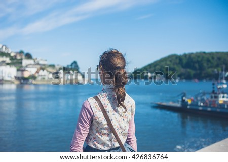 A young woman is standing by the water in a small village on a sunny summer day - stock photo