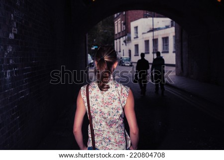A young woman is standing in a tunnel - stock photo