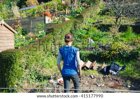 A young woman is standing in her garden on a sunny day - stock photo