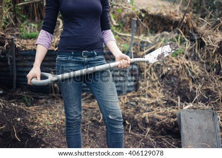 A young woman is standing in her garden with a spade