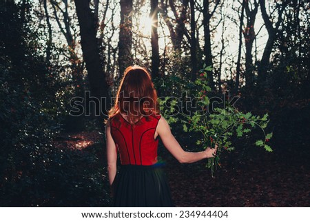 A young woman is standing in the forest with a bunch of holly in her hand - stock photo