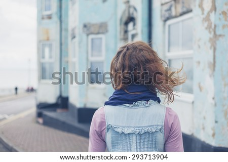 A young woman is standing in the street outside a blue house by the coast on a windy day