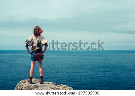 A young woman is standing on a rock by the sea