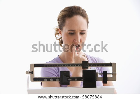 A young woman is standing on her scale and checking her weight. She has a worried expression on her face. Horizontal shot. Isolated on white.