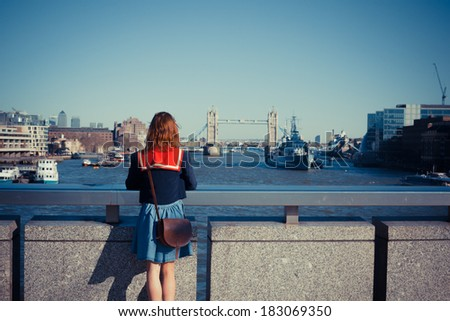 A young woman is standing on London bridge and admiring the skyline and the river Thames