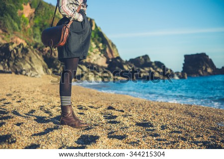 A young woman is standing on the beach on a sunny day in the autumn - stock photo