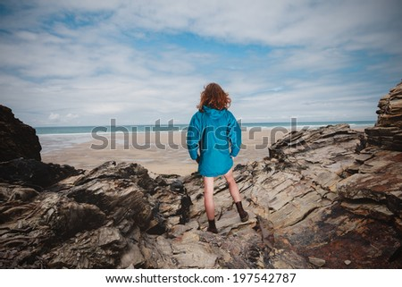 A young woman is standing on the coast and is looking at the sea