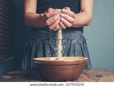 A young woman is standing with a handful of oats - stock photo