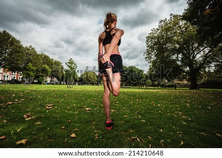 A young woman is stretching and working out in the park - stock photo