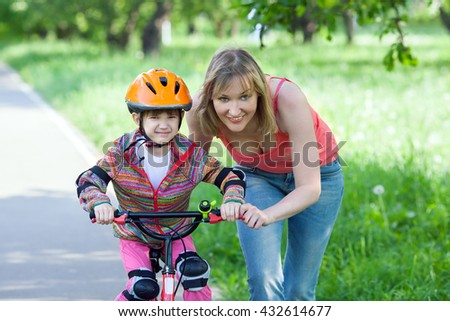 A young woman is teaching girl to ride bicycle in summer park