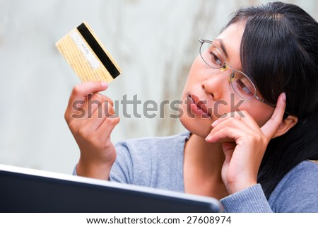A young woman is thinking about using her credit card.