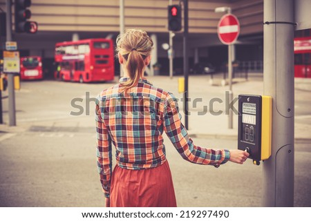 A young woman is waiting to cross the road - stock photo