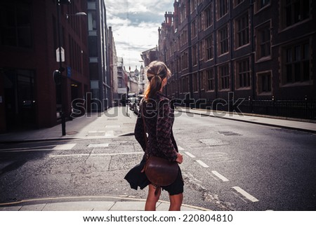 A young woman is walking in the street and is looking at the architecture