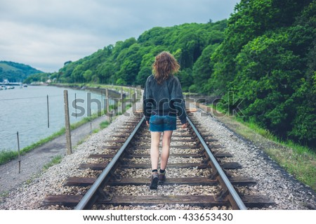 A young woman is walking on the railroad tracks - stock photo