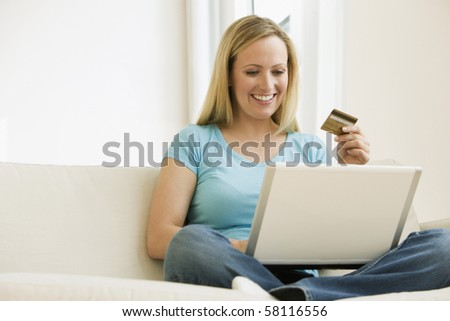 A young woman is working on a laptop and holding up her credit card.  Horizontal shot.