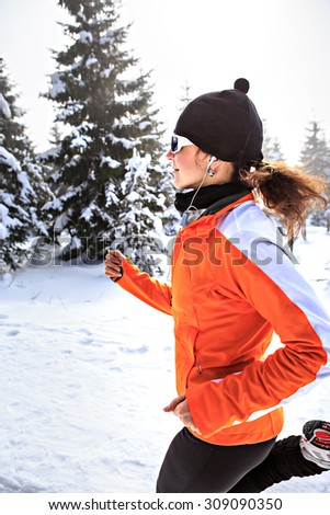 A young woman jogging in the wintry forest - stock photo