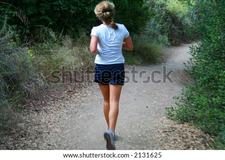 A young woman jogging on a trail. - stock photo