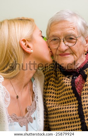 A young woman kissing an older one  (focus on the elderly) - part of a series. - stock photo