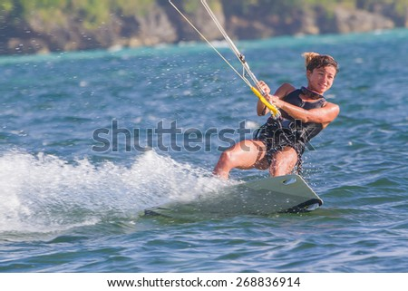 A young woman kite-surfer rides in blue sea - stock photo