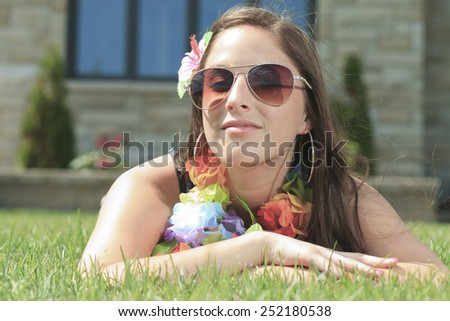 A young woman lay down and take a rest on the green grass - stock photo