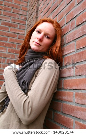 A young woman leaning against a brick wall.
