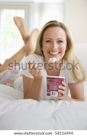 A young woman lies on her bed while eating a pint of ice cream. She is smiling at the camera.  Vertical shot.