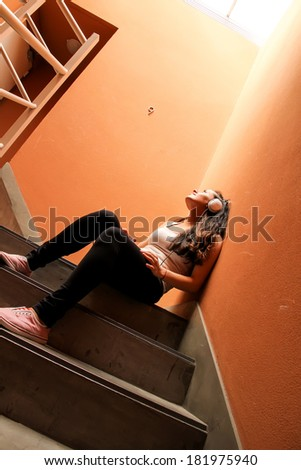 A young woman listening to melancholic Music sitting in the stairway. - stock photo