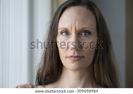 A young woman looking at camera, blank expression - stock photo