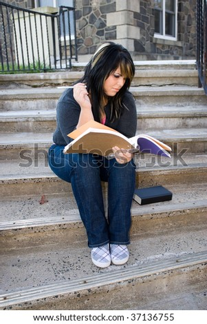 A young woman looking at her notebook while sitting on the campus stairs. - stock photo