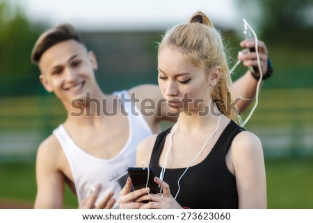 a young woman looking back on the phone and her friend who laughs - stock photo