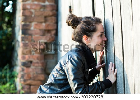 A young woman looking into the old building through the closed gate. - stock photo