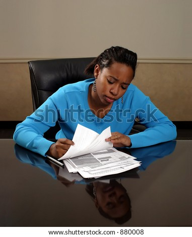 A young woman looking through paperwork. - stock photo