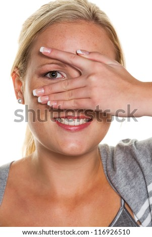 a young woman looking through the fingers of her hand. symbolic photo for clear view and flirt - stock photo