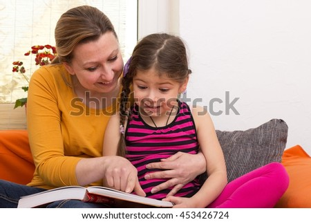 A young woman looking with a girl looking into a book