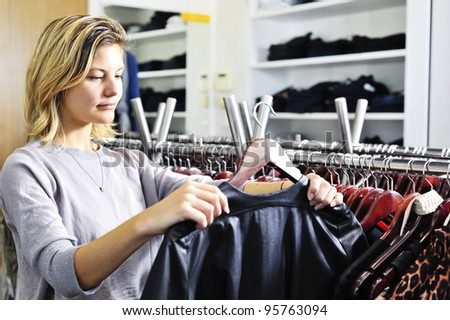 "a young woman looks at a jacket in a clothing store; this model has a very natural ""normal"" look. - stock photo"
