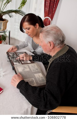 a young woman looks at a photo album with seniors