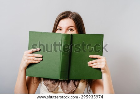 A young woman looks out of a book. On a gray background. - stock photo